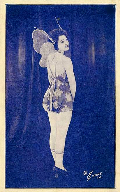 arcade-card-evans-l-a-woman-dressed-as-fairy-back-to-camera-looking-over-shoulder-1920s