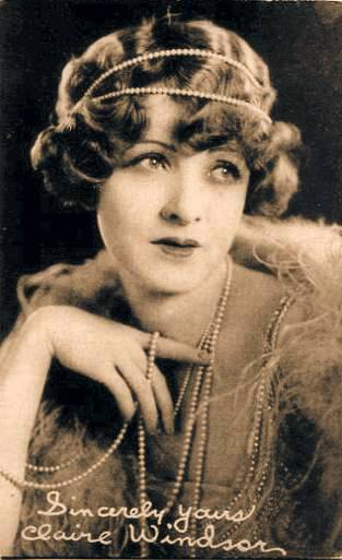 arcade-card-exhibit-supply-company-movie-star-claire-windsor-almost-full-face-eyes-up-fingering-pearls-1920s