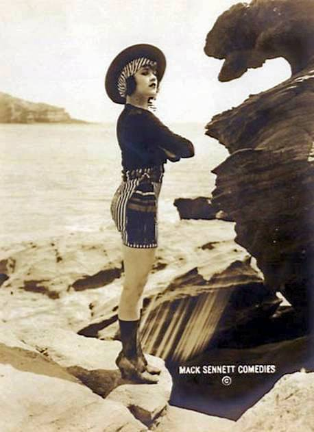 arcade-card-mack-sennett-comedies-movie-star-harriet-hammond-standing-profile-on-rocks-with-shorts-and-coordinating-hat-1920s