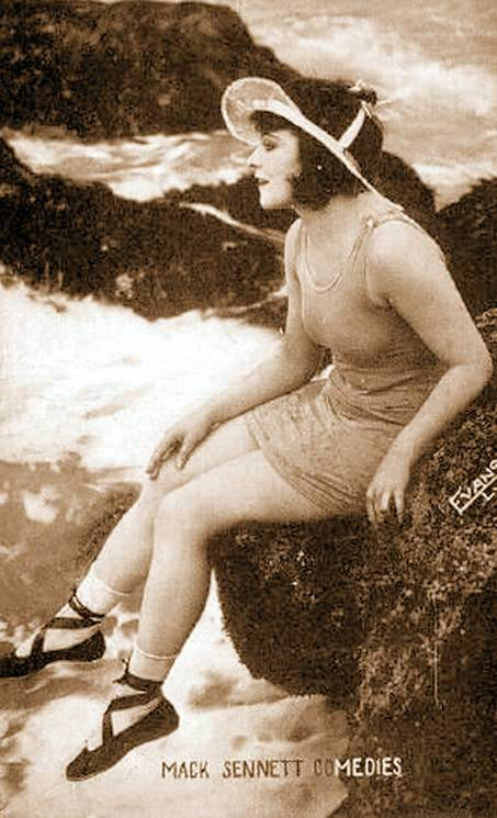 arcade-card-mack-sennett-comedies-movie-star-mary-thurmond-sitting-on-rocks-in-dress-like-bathing-suit-profile-1920s