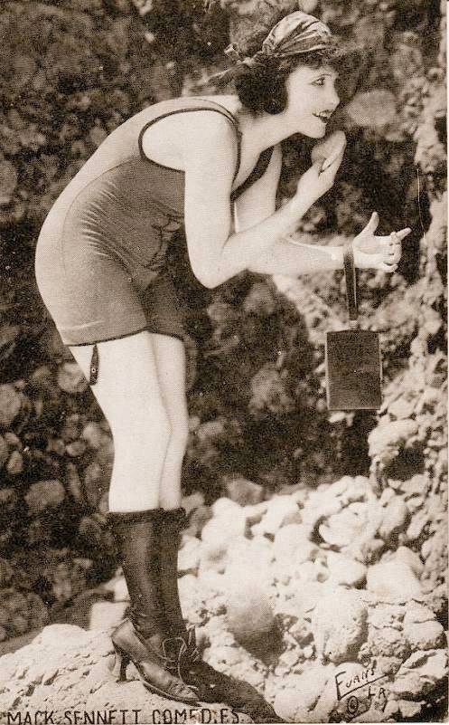 arcade-card-mack-sennett-comedies-woman-in-bathing-suit-and-head-band-bending-over-on-rocks-to-touch-up-her-make-up