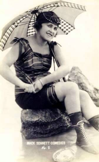 arcade-card-mack-sennett-comedies-woman-sitting-on-rock-in-bathing-suit-with-parasol-and-boots