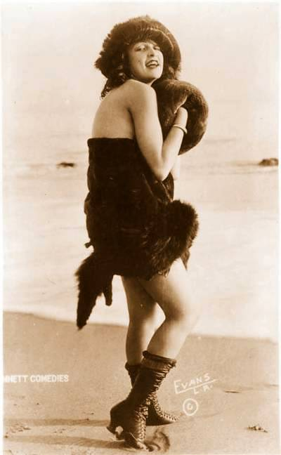 arcade-card-mack-sennett-comedies-woman-standing-on-beach-in-fur-hat-and-muff-and-suit-1920s