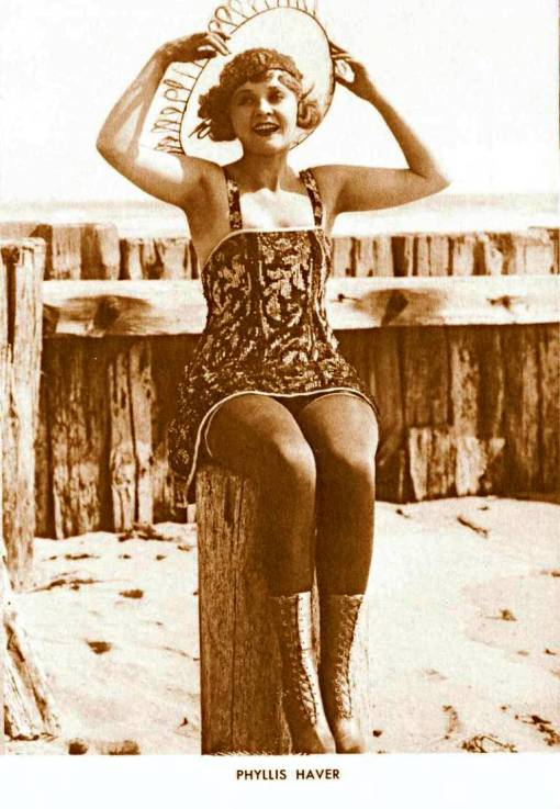 arcade-card-movie-star-phyllis-haver-sitting-on-pier-post-in-sun-dress-with-hat-and-boots-1920s