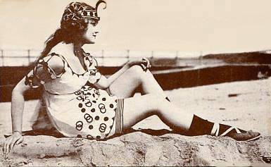 arcade-card-woman-in-skirt-like-bathing-suit-and-vaguely-egyptian-head-piece-sitting-on-rocks-profile
