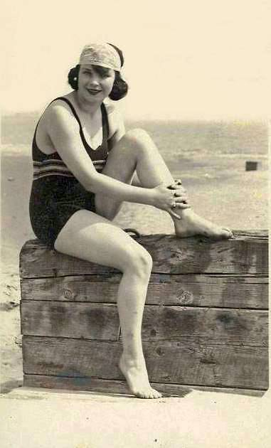 arcade-card-woman-in-wooly-bathing-suit-and-head-band-sitting-on-wooden-wall-by-beach-1920s