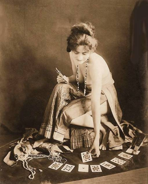 photo-for-arcade-card-exhibit-supply-company-woman-sitting-in-gypsy-like-outfit-with-cards-spread-on-floor-sepia-1920s