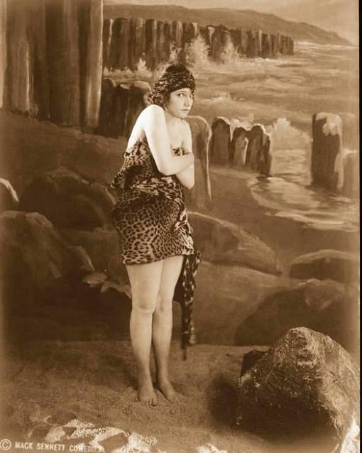 photo-for-arcade-card-mack-sennett-comedies-woman-in-leopard-suit-and-hat-standing-on-sea-set-1920s