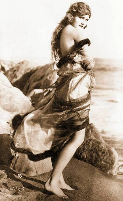 photo-for-arcade-card-movie-star-harriet-hammond-standing-profile-on-beach-windswept-clothes-looking-towards-camera-1920s