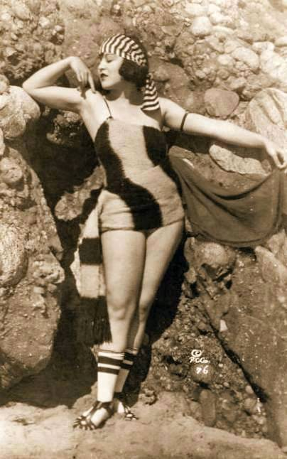 photo-for-arcade-card-movie-star-marie-prevost-standing-by-rocks-in-head-band-and-wooly-bathing-suit-1920s