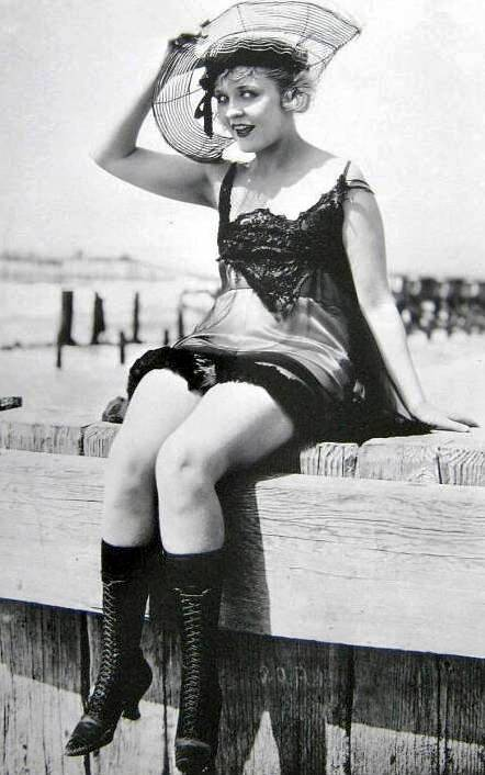 photo-for-arcade-card-movie-star-phyllis-haver-sitting-on-fence-in-satiny-bathing-suit-holding-her-hat-on
