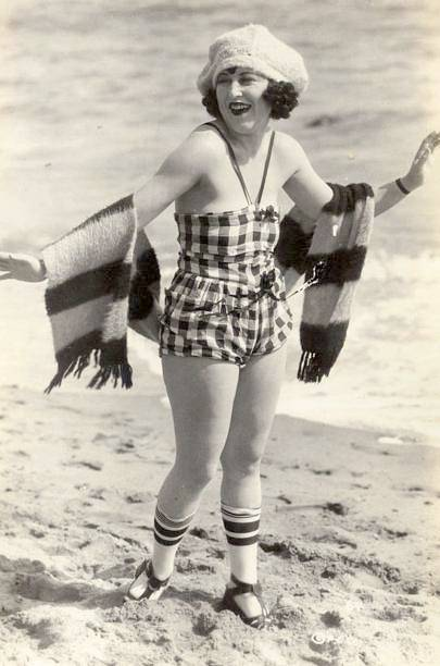 photo-for-arcade-card-movie-star-vera-steadman-in-check-bathing-suit-big-bonnet-and-striped-scarf-on-beach
