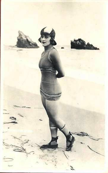 photo-for-arcade-card-woman-arms-behind-her-in-wooly-bathing-suit-and-cap-and-sandals-on-beach-1920s