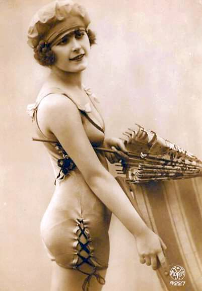 photo-for-arcade-card-woman-by-beach-chair-in-satiny-bathing-suit-with-ties-on-the-side-and-cap