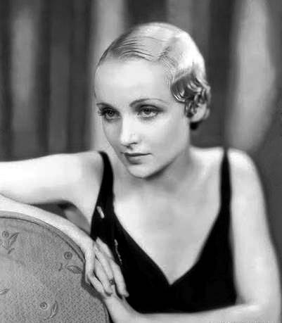photo-movie-star-carole-lombard-arms-over-back-of-chair-hair-slicked-down