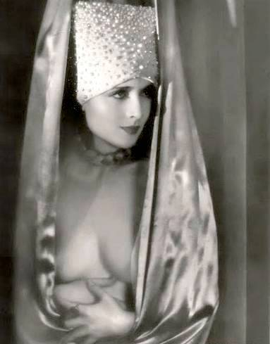 photo-movie-star-carole-lombard-satiny-exotic-outfit-partly-open-at-front-hands-resting-under-breast-head-three-quarters