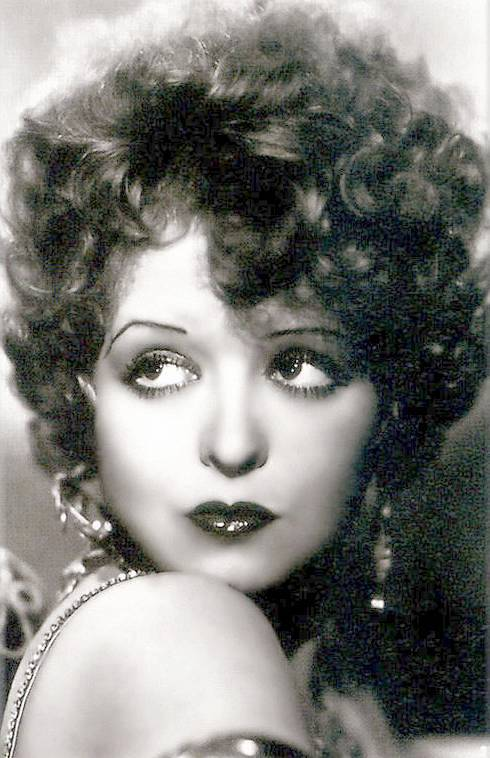 photo-movie-star-clara-bow-heavily-made-up-gold-earrings-and-dress-strap-looking-over-shoulder