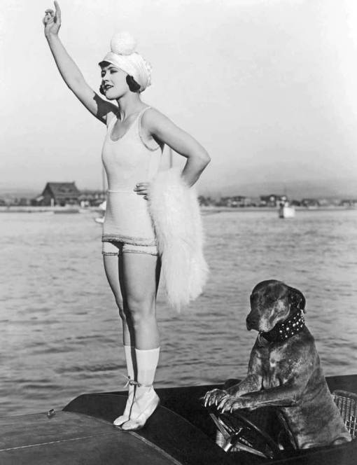 photo-movie-star-gloria-swanson-standing-on-boat-in-bathing-suit-and-cap-arm-raised-her-dog-next-to-her-1920s