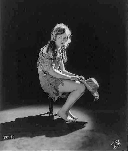 studio-portrait-for-mack-sennett-comedies-woman-sitting-on-stool-in-ragged-outfit-with-hanging-curls-holding-straw-hat