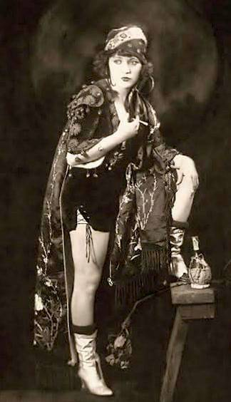 studio-portrait-movie-star-marie-prevost-standing-in-gypsy-like-costume-with-cigarette-and-one-leg-up-1920s