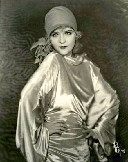 studio-portrait-movie-star-phyllis-haver-satiny-evening-dress-and-hat-almost-like-a-head-scarf-hands-on-hips-handsome-image-1920s