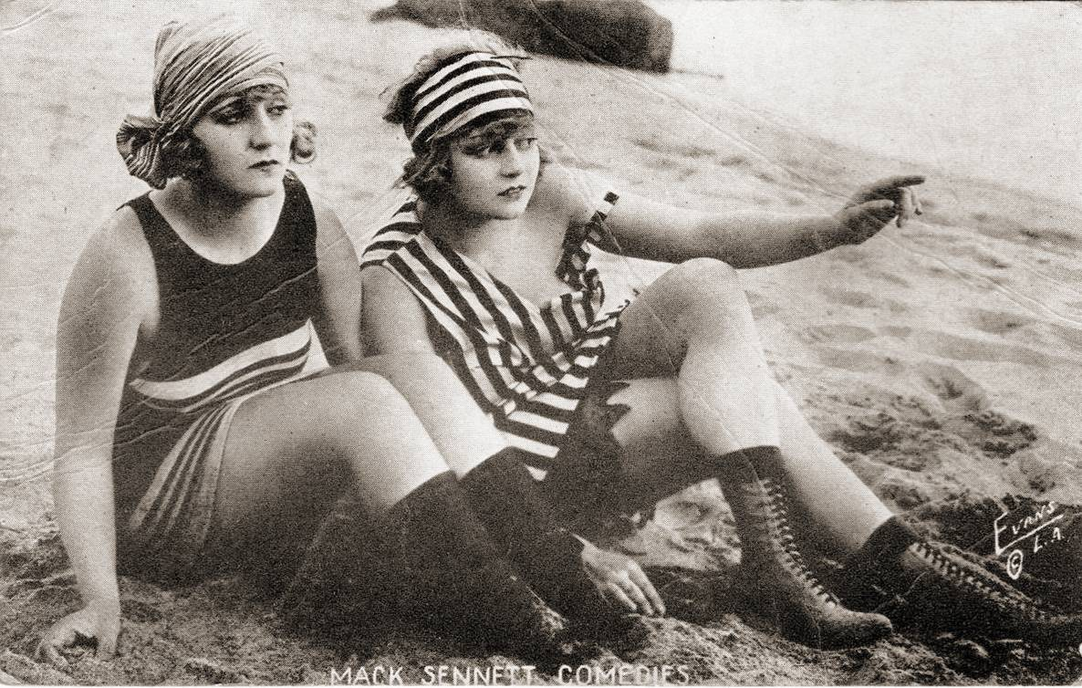 ARCADE CARD MACK SENNETT COMEDIES TWO WOMEN SITTING ON BEACH WITH HEAD WRAPS AND TALL BOOTS