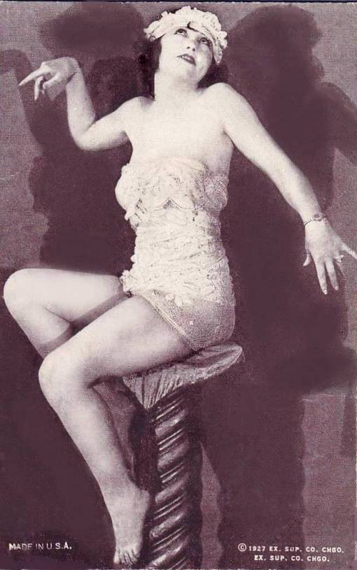 arcade-card-exhibit-supply-company-pin-up-woman-in-nightie-with-headband-sitting-on-tall-stool-with-arms-gracefully-spread-1927
