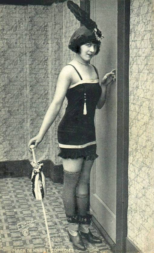 arcade-card-mack-sennett-comedies-woman-in-bathing-suit-and-feathered-bonnet-standing-by-door