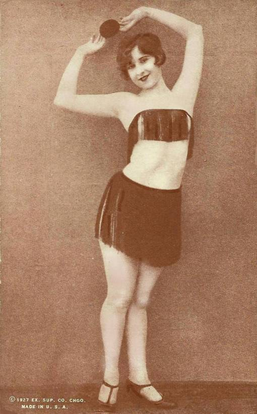 ARCADE CARD - EXHIBIT SUPPLY COMPANY - PIN-UP - WOMAN STANDING IN TASSELLED TOP AND SKIRT WITH HANDS OVER HEAD - 1927