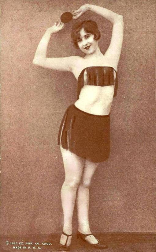 arcade-card-exhibit-supply-company-pin-up-woman-standing-in-tasselled-top-and-skirt-with-hands-over-head-1927