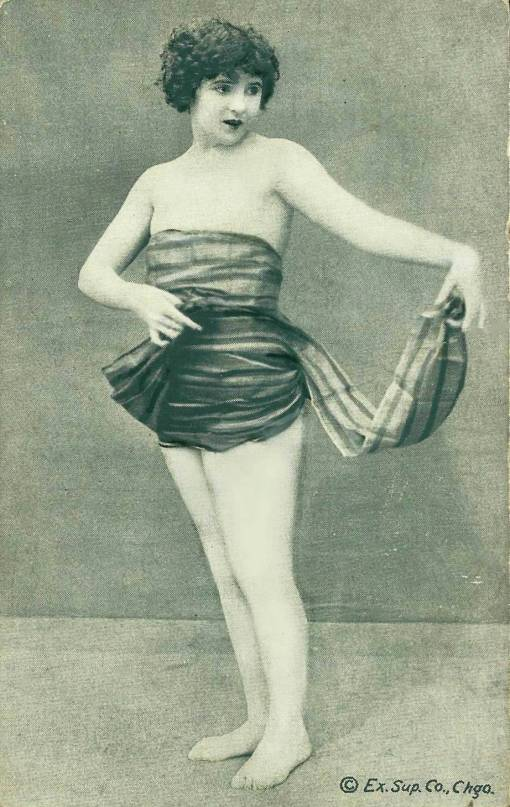 ARCADE CARD - EXHIBIT SUPPLY COMPANY - PIN-UP - WOMAN WITH BOBBED HAIR STANDING HOLDING END OF WRAP COVERING HER - 1920s