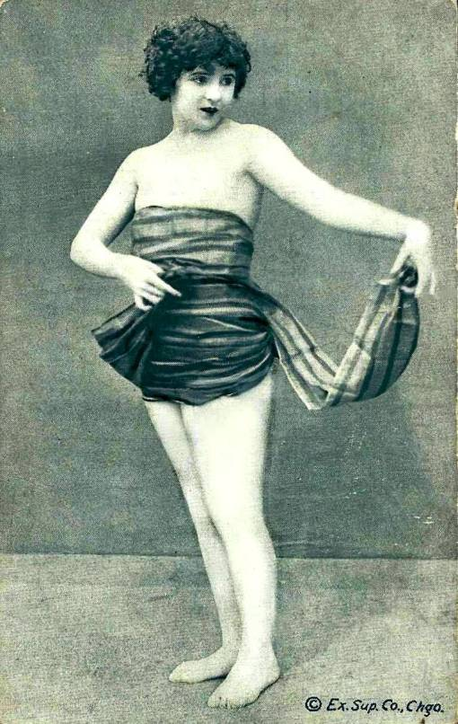arcade-card-exhibit-supply-company-pin-up-woman-with-bobbed-hair-standing-holding-end-of-wrap-covering-her-1920s