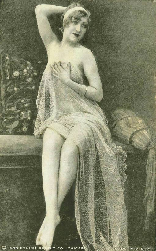 ARCADE CARD - EXHIBIT SUPPLY COMPANY - PIN-UP - WOMAN WITH HEADBAND AND ONE HAND BEHIND HER HEAD SITTING ON BENCH HOLDING LACE DRAPE - 1930