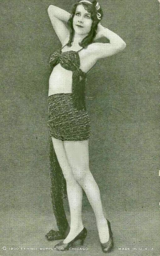 arcade-card-exhibit-supply-company-pin-up-woman-with-long-spring-curls-and-hands-behid-head-standing-in-two-piece-outfit-1930