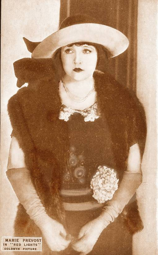 ARCADE CARD - GOLDWYN PICTURES - MOVIE STAR - MARIE PREVOST IN RED LIGHTS - STANDING IN WIDE-BRIMMED HAT FACE TO CAMERA EYES TURNED