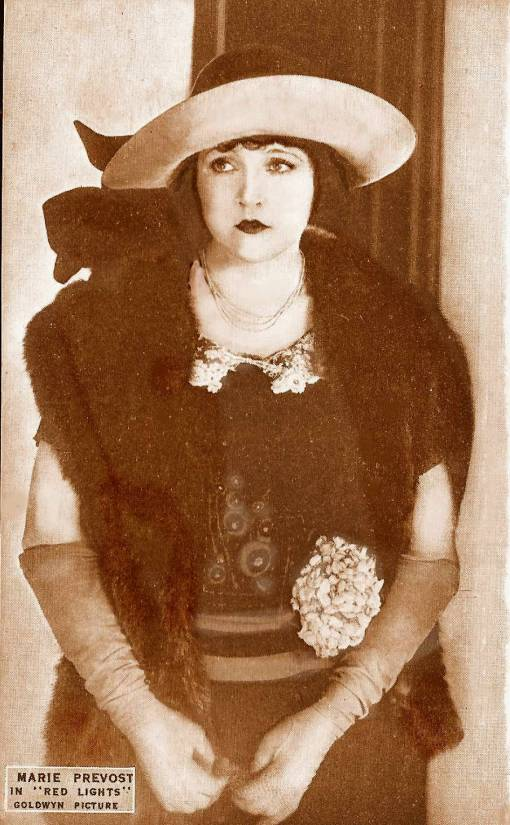 arcade-card-goldwyn-pictures-movie-star-marie-prevost-in-red-lights-standing-in-wide-brimmed-hat-face-to-camera-eyes-turned