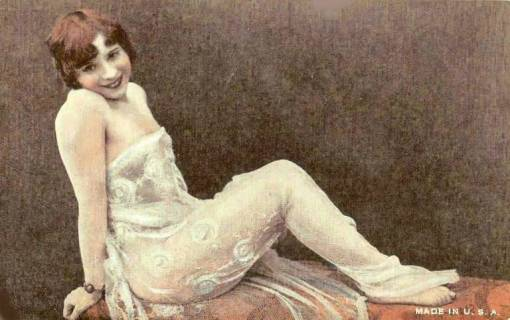 arcade-card-unknown-publisher-style-is-exhibit-supply-company-pin-up-woman-with-bobbed-hair-in-lace-sitting-on-table-tinted-1920s
