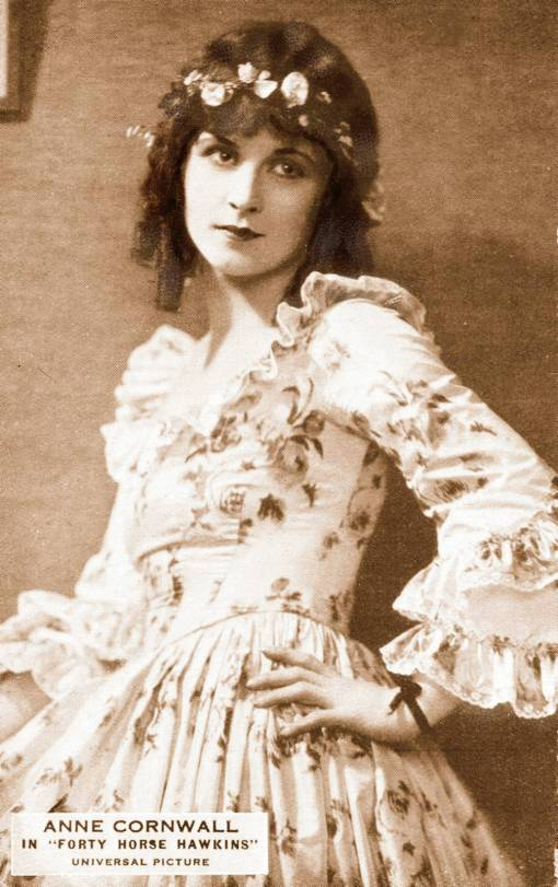ARCADE CARD - MOVIE STAR - ANEE CORNWALL - IN FORTY HORSE HAWKINS - LEANING AGAINST WALOL HAND TO HIP FRILLY DRESS AND SPRING CURLS