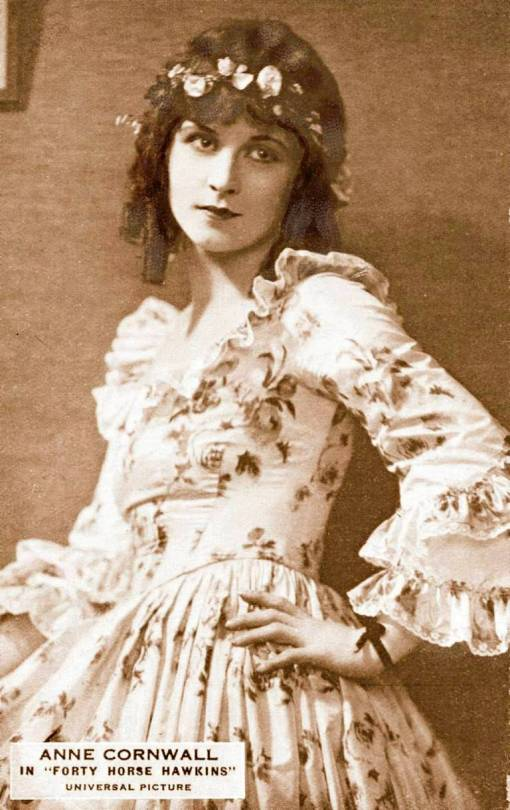 arcade-card-movie-star-anee-cornwall-in-forty-horse-hawkins-leaning-against-walol-hand-to-hip-frilly-dress-and-spring-curls