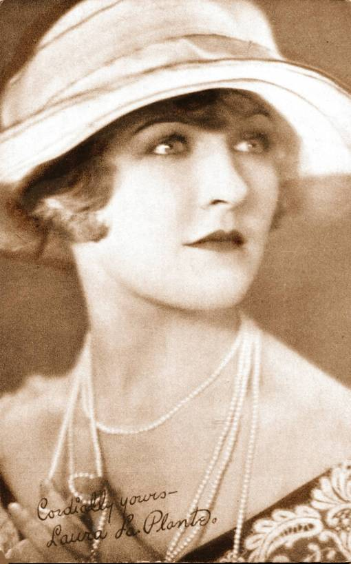 ARCADE CARD - MOVIE STAR - LAURA LA PLANTE - THREE-QUARTERS LOOKING UP IN BIG-BRIMMED HAT AND STRINGS OF PEARLS