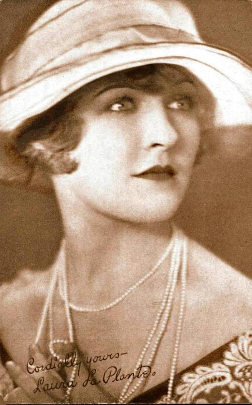 arcade-card-movie-star-laura-la-plante-three-quarters-looking-up-in-big-brimmed-hat-and-strings-of-pearls