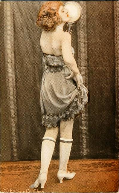 ARCADE CARD - EXHIBIT SUPPLY COMPANY - PIN -UP - RED-HAIRED WOMAN IN DARK SLIP LOOKING AT MIRROR WITH BACK TO CAMERA - TINTED SERIES - 1920s