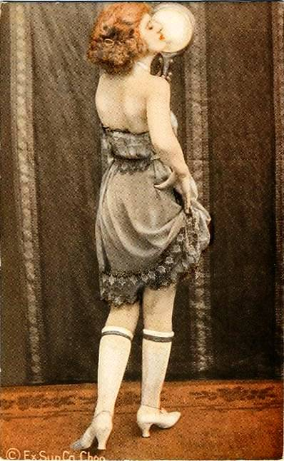 arcade-card-exhibit-supply-company-pin-up-red-haired-woman-in-dark-slip-looking-at-mirror-with-back-to-camera-tinted-series-1920s.jpg