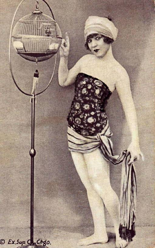 arcade-card-exhibit-supply-company-pin-up-woman-in-veil-headband-standing-by-bird-cage-late-1920s
