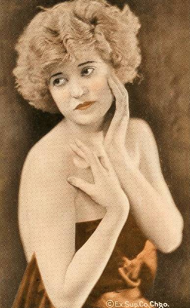 ARCADE CARD - EXHIBIT SUPPLY COMPANY - WOMAN WITH BOBBED LIGHT HAIR AND HANDS GRACEFULLY AROUND FACE - 1920s