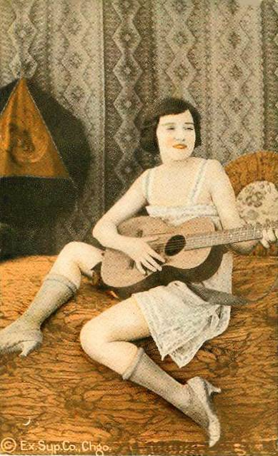 ARCADE CARD - EXHIBIT SUPPLY - PIN-UP - WOMAN IN NIGHTIE AND STOCKINGS WITH GUITAR ON BED - TINTED SERIES - 1920s