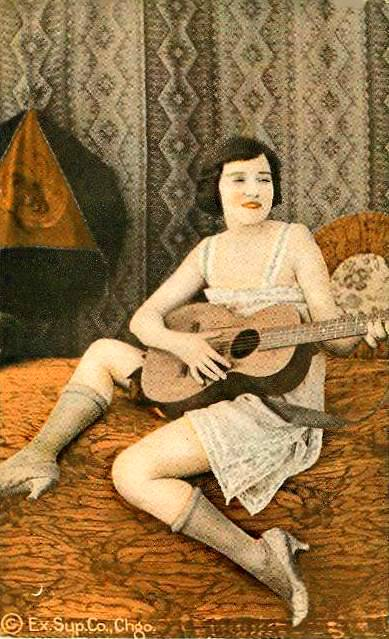 arcade-card-exhibit-supply-pin-up-woman-in-nightie-and-stockings-with-guitar-on-bed-tinted-series-1920s
