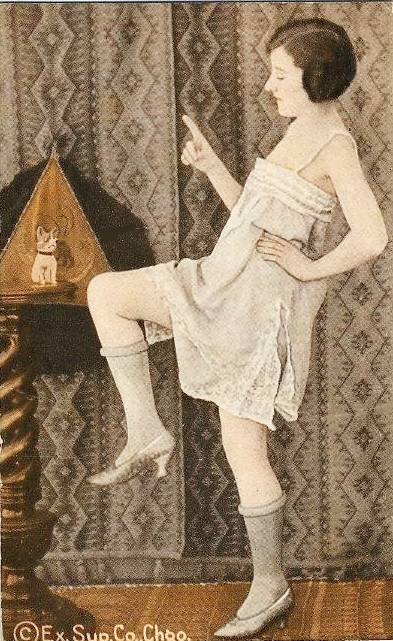 ARCADE CARD - EXHIBIT SUPPLY COMPANY - PIN-UP - WOMAN IN NIGHTIE AND BOBBED HAIR WITH DANCE POSE AND FINGER WAVING AT ANIMAL DOLL - TINTED - 1920s
