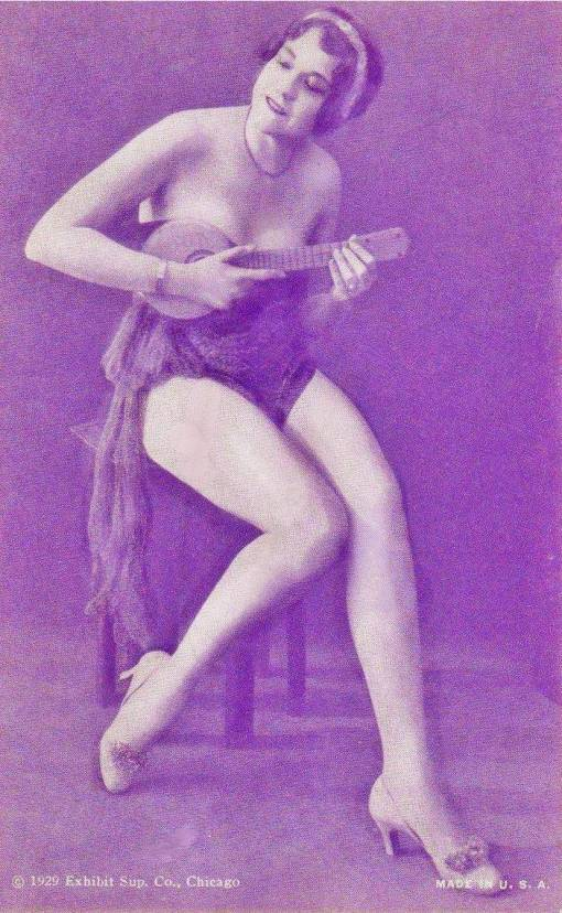 ARCADE CARD - EXHIBIT SUPPLY COMPANY - PIN-UP - WOMAN WITH HEAD BAND SITTING ON A STOOL PLAYING A SMALL STRINGED INSTRUMENT - 1929