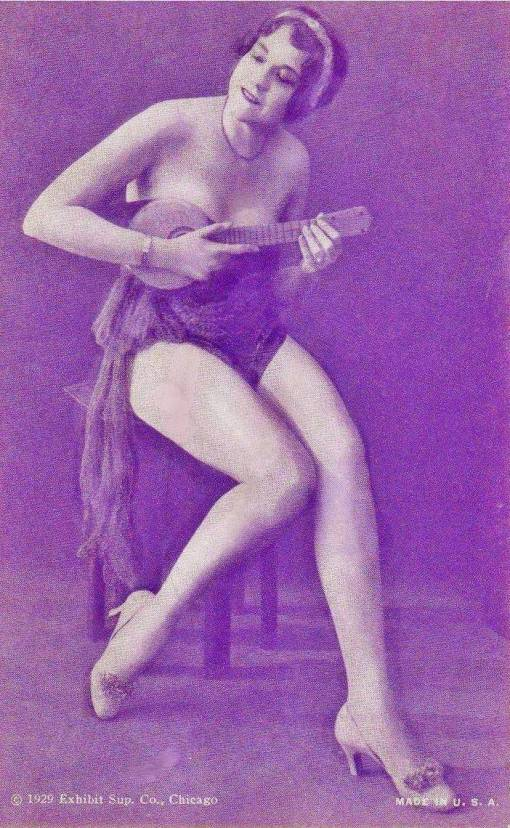 arcade-card-exhibit-supply-company-pin-up-woman-with-head-band-sitting-on-a-stool-playing-a-small-stringed-instrument-1929